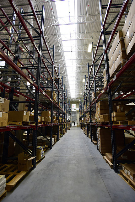 Inside the warehouse, tall shelving lines left and right walls